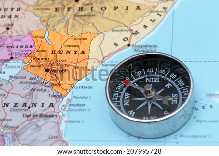 Compass on a map pointing at Kenya and planning a travel destination - stock photo