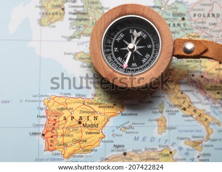 Compass on a map pointing at Spain and planning a travel destination - stock photo