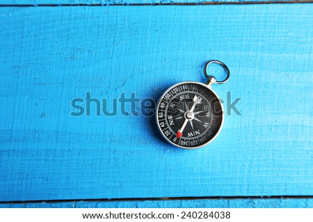 Compass on blue wooden background - stock photo