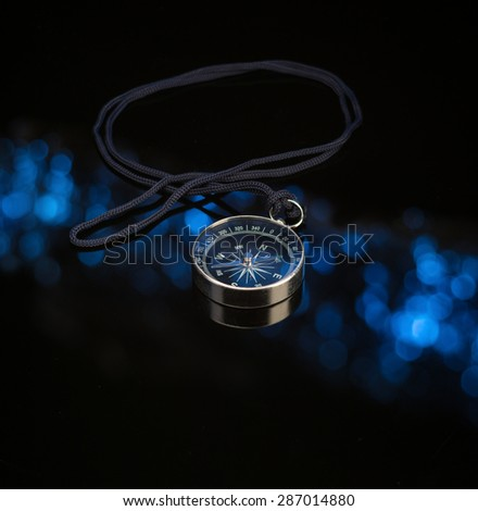 Compass on dark background with blue defocused lights - stock photo