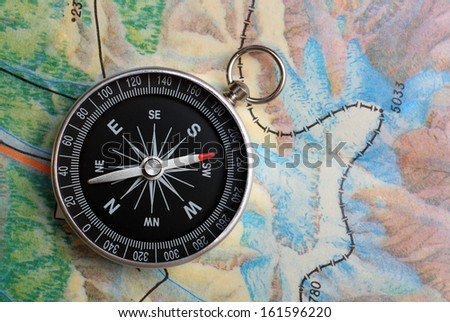 compass on geography map - orientation concept - stock photo