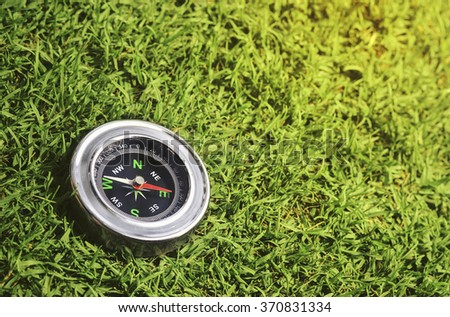 compass on green grass background - stock photo