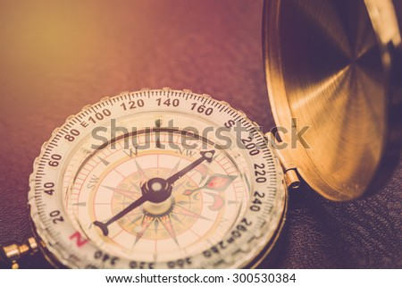 Compass on leather background close up. Vintage filter.
