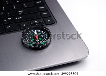 Compass on notebook keyboard, conceptual image.