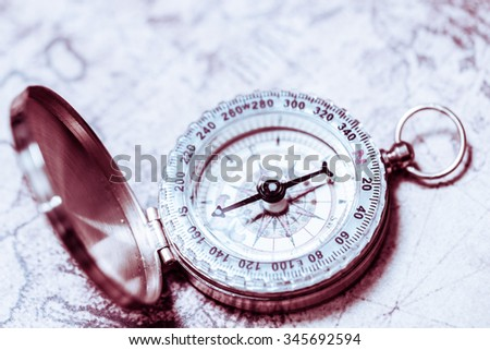 Compass on old vintage map. Retro filter. - stock photo
