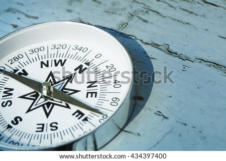 compass on old wood painted table - stock photo
