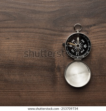 compass on the brown wooden table background - stock photo