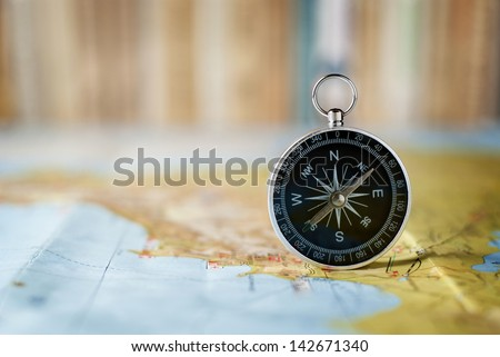 compass on the map and book in the background in the area of confusion - stock photo