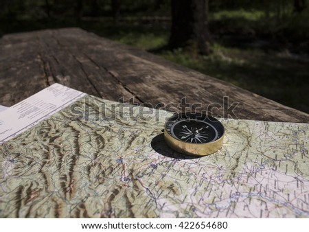 compass on the map/magnetic compass standing upright on a world map conceptual of global travel/the time-tested Navigator - stock photo