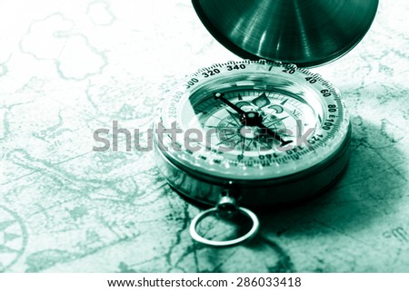 Compass on vintage map. Retro filter. - stock photo