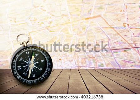 compass on wooden floor with blur road map background