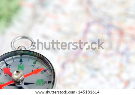 Compass photoed against the background of the map. - stock photo