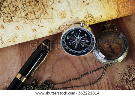 Compass ,pocket watch and Fountain pen on vintage map. Retro style. - stock photo