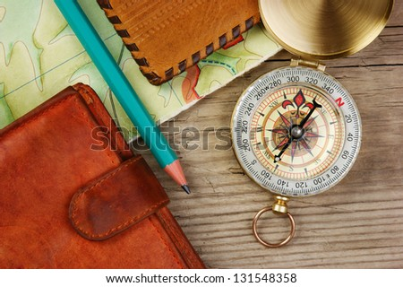 compass wallet and passport on a wooden table - stock photo