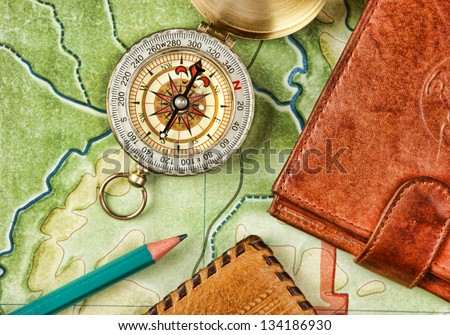compass wallet and passport on the old map - stock photo