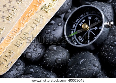 Compass with credit card ,rock cover water drop - stock photo