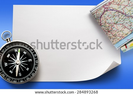 Compass with map on blank piece of paper - stock photo