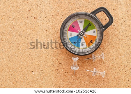 Compass with Push Pins on Cork Surface - stock photo