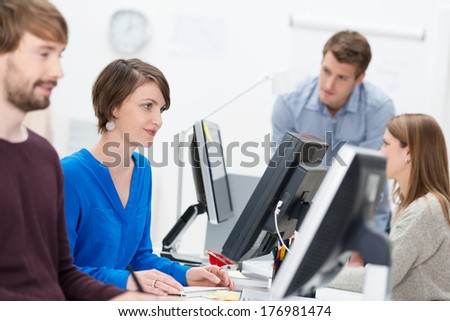 Competent businesswoman working in a busy office sitting smiling at her desktop computer surrounded by hardworking colleagues - stock photo