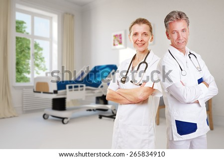 Competent team in nursing home with doctor and nurse in empty room - stock photo