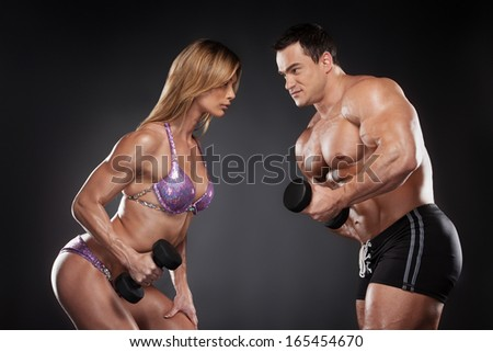 Competition between female and male bodybuilder. Standing isolated over black background and looking at each other.