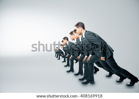 Competition concept with businessmen about to run on grey background - stock photo