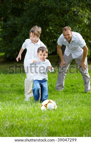 Competition of two little brothers in football in a summer garden - stock photo