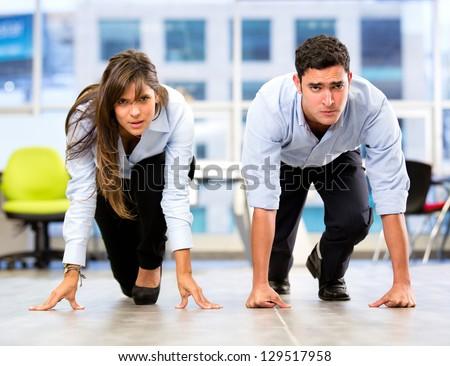 Competitive business couple racing at the office - stock photo