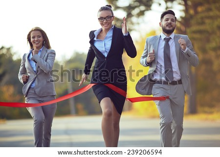 Competitive businesswoman coming to finish first with her colleagues behind - stock photo