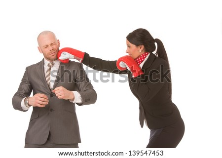 Competitive businesswoman, wearing boxing-gloves, knocks-out male competitor by punching him on the chin. Conceptual image.