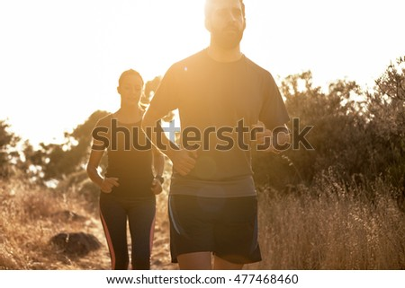 Competitive couple jogging up a gravel path in the late afternoon sunshine with mountains behind, while wearing casual clothing