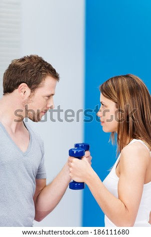 Competitive young couple working out at the gym facing off staring at each other as they work out with dumbbells in a health and fitness concept - stock photo