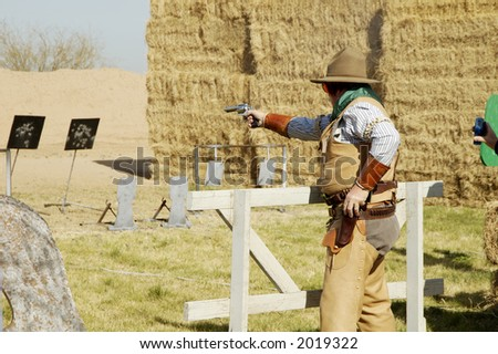 Competitor shooting a single-action pistol in a cowboy shoot competition.