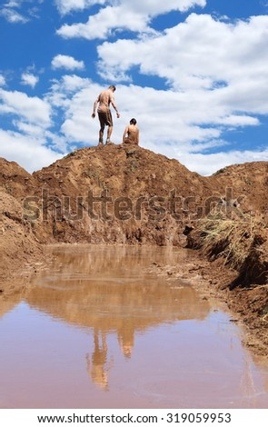 Competitors running through a mud pit and up a hill at a Mud Race
