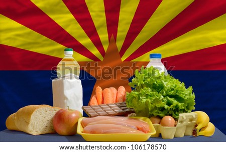 complete american state flag of arizona covers whole frame, waved, crunched and very natural looking. In front plan are fundamental food ingredients for consumers, symbolizing consumerism - stock photo