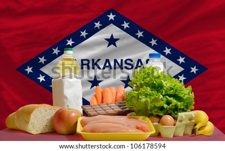 complete american state flag of arkansas covers whole frame, waved, crunched and very natural looking. In front plan are fundamental food ingredients for consumers, symbolizing consumerism - stock photo