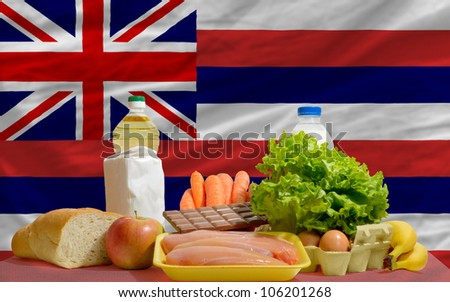 complete american state flag of hawaii covers whole frame, waved, crunched and very natural looking. In front plan are fundamental food ingredients for consumers, symbolizing consumerism