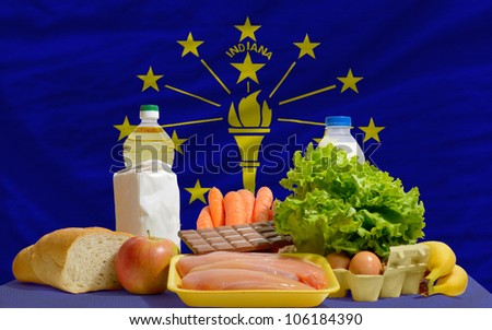 complete american state flag of indiana covers whole frame, waved, crunched and very natural looking. In front plan are fundamental food ingredients for consumers, symbolizing consumerism - stock photo