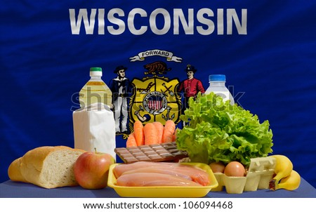 complete american state flag of wisconsin covers whole frame, waved, crunched and very natural looking. In front plan are fundamental food ingredients for consumers, symbolizing consumerism - stock photo