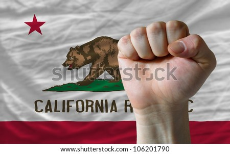 complete american state of california flag covers whole frame, waved, crunched and very natural looking. In front plan is clenched fist symbolizing determination - stock photo
