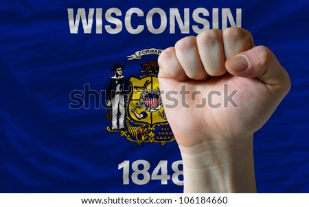 complete american state of wisconsin flag covers whole frame, waved, crunched and very natural looking. In front plan is clenched fist symbolizing determination - stock photo