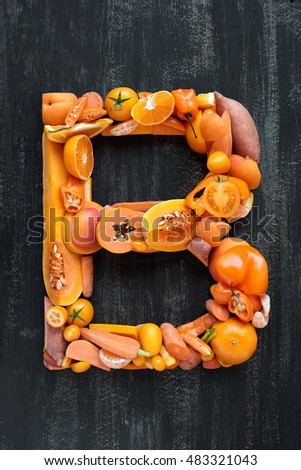 complete collection of alphabet letters made from healthy orange fruit and vegetables on rustic distressed texture, overhead flat lay