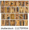 complete English alphabet - collage of 26 isolated vintage wood letterpress printing blocks, scratched and stained by ink patina, gothic bold extended font - stock photo