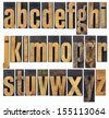 complete English lowercase alphabet - a collage of 26 isolated antique wood letterpress printing blocks, scratched and stained by inks - stock photo