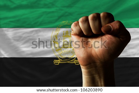 complete national flag of afghanistan covers whole frame, waved, crunched and very natural looking. In front plan is clenched fist symbolizing determination - stock photo