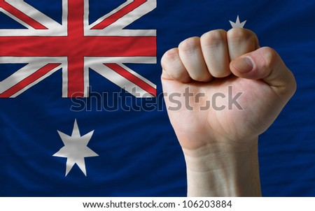 complete national flag of australia covers whole frame, waved, crunched and very natural looking. In front plan is clenched fist symbolizing determination - stock photo