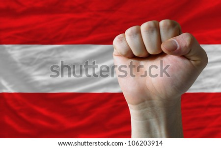 complete national flag of austria covers whole frame, waved, crunched and very natural looking. In front plan is clenched fist symbolizing determination - stock photo