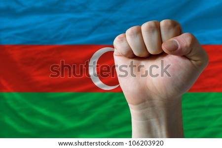 complete national flag of azerbaijan covers whole frame, waved, crunched and very natural looking. In front plan is clenched fist symbolizing determination - stock photo