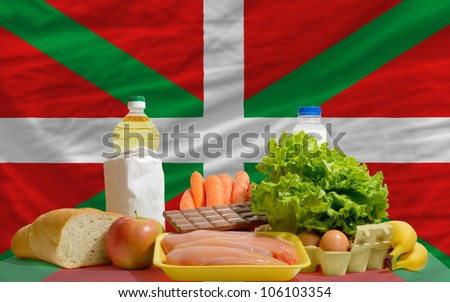 complete national flag of basque covers whole frame, waved, crunched and very natural looking. In front plan are fundamental food ingredients for consumers, symbolizing consumerism an human needs - stock photo