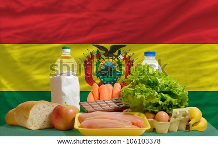 complete national flag of bolivia covers whole frame, waved, crunched and very natural looking. In front plan are fundamental food ingredients for consumers, symbolizing consumerism an human needs - stock photo